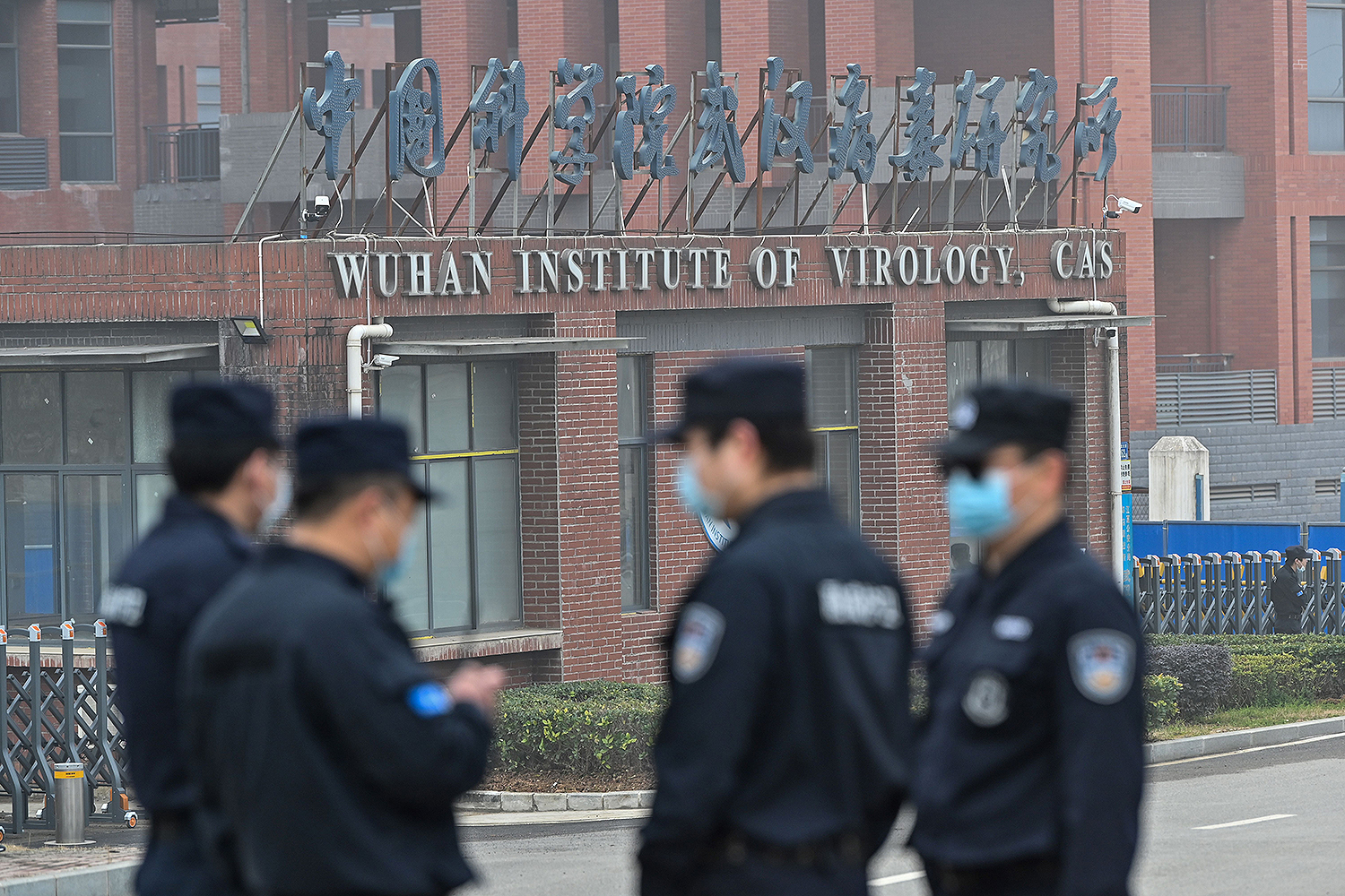 Security personnel stand guard outside the Wuhan Institute of Virology in Wuhan, China, during a visit by members of the World Health Organization team investigating the origins of COVID-19 on Feb. 3.