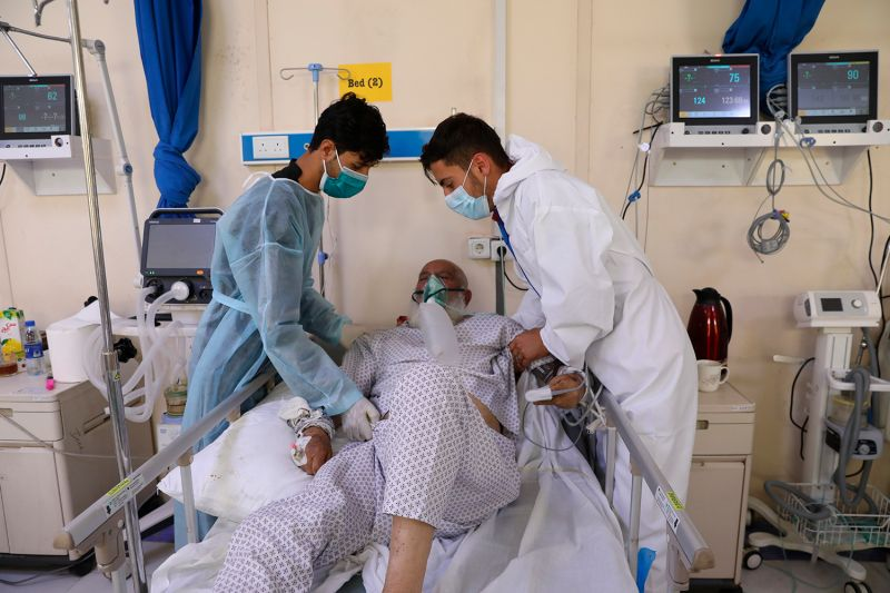 Sons help their father at an Afghan hospital.