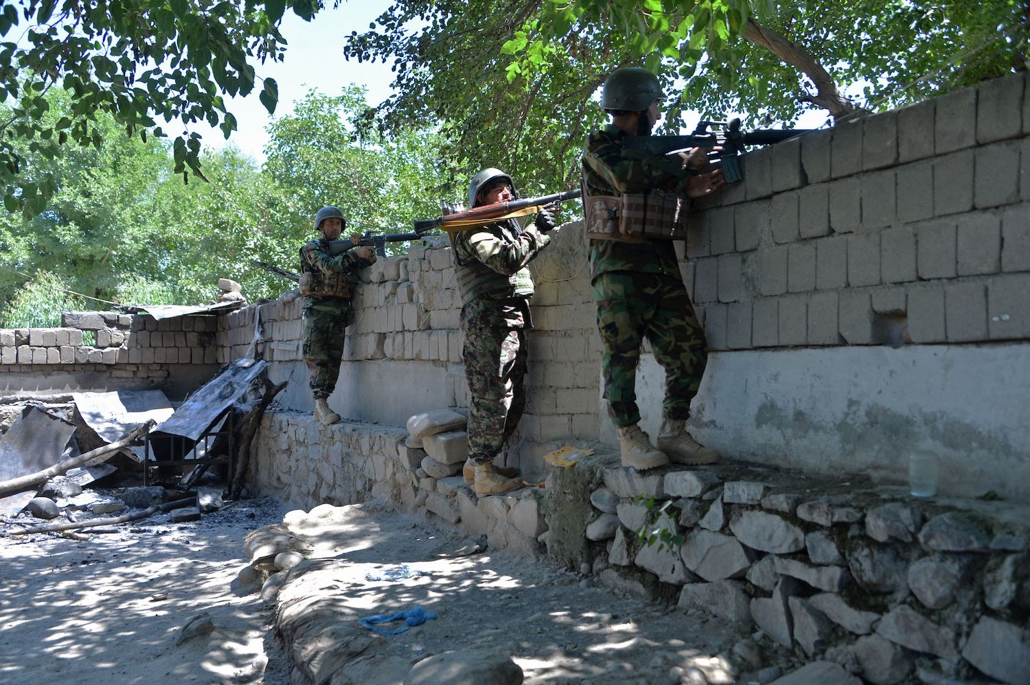 Afghan security forces take their positions during a clash with Afghan forces in Mihtarlam, Afghanistan, on May 24.