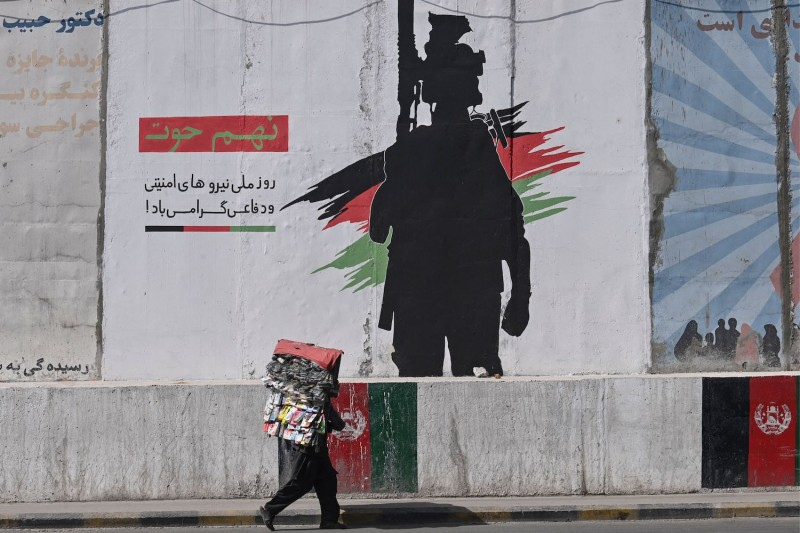 A street vendor walks past a mural depicting an Afghan National Army soldier in Kabul on June 10.