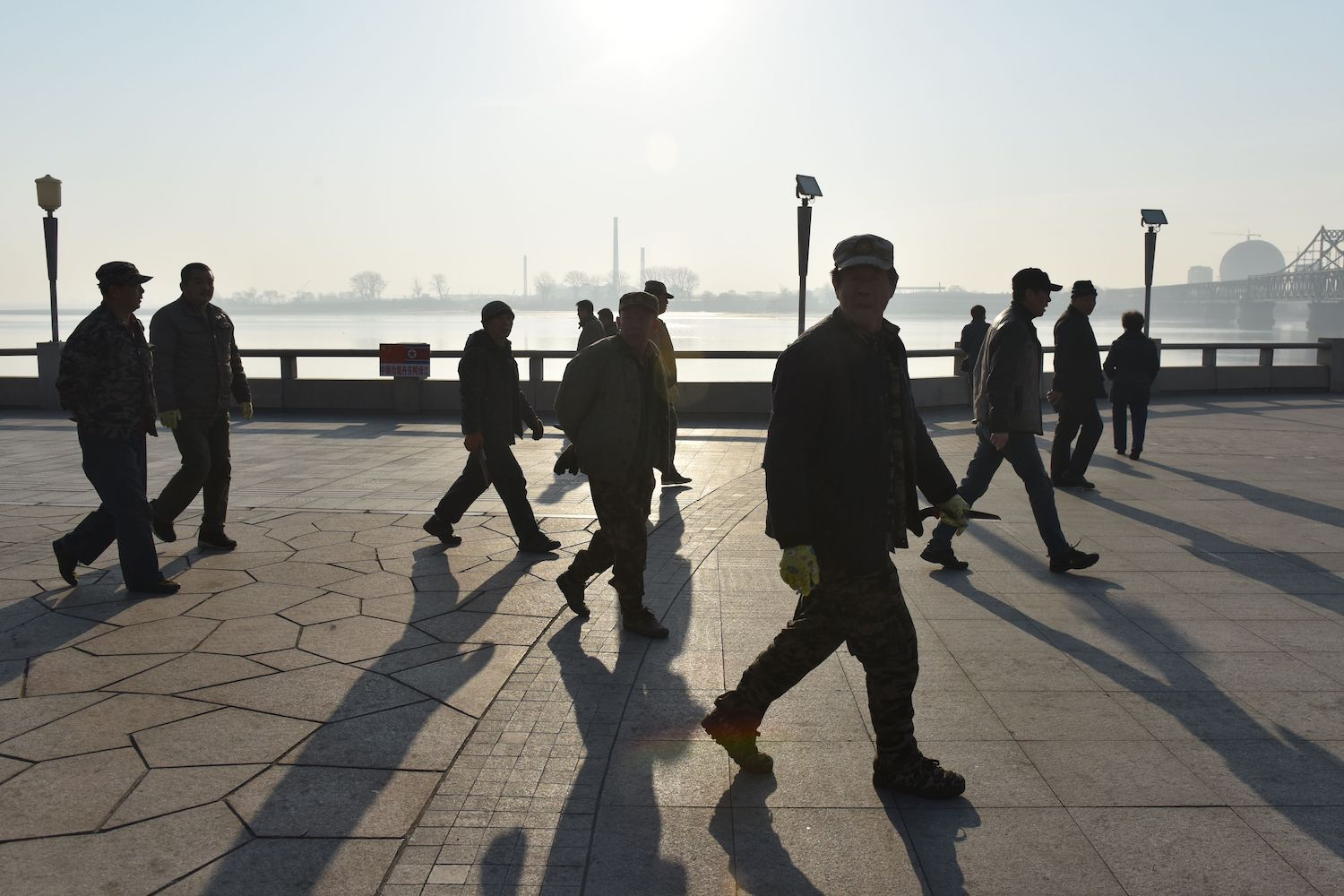 Workers walk on the waterfront in Dandong, China, with the North Korean city of Sinuiju in the background, on Feb. 23, 2019.