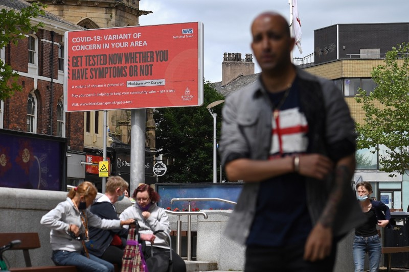 A pedestrian walks past an electronic board displaying information about COVID-19 in Blackburn, England.