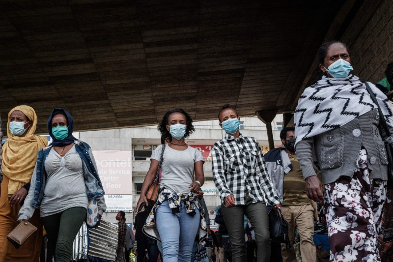 Women wearing masks walk under an overpass in Addis Ababa on June 17.
