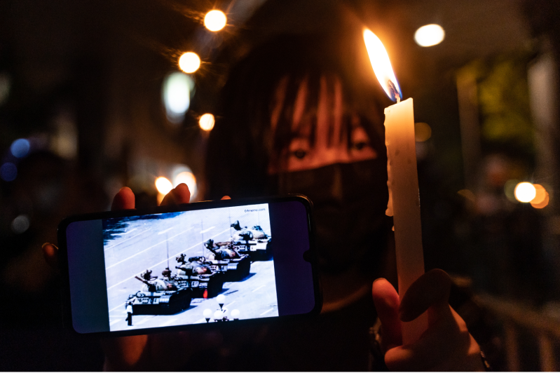 A protester holds a candle and a cellphone in Hong Kong.