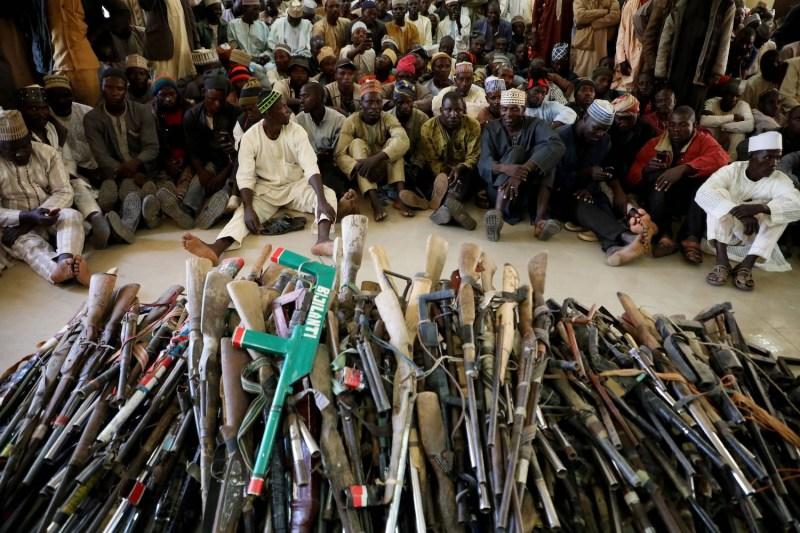 Yansakai vigilante members surrender their guns.