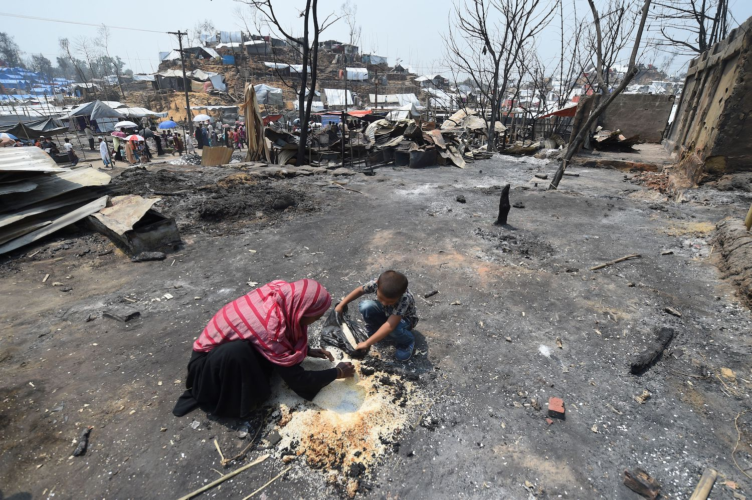 A Rohingya refugee family collects rice after a fire at a refugee camp in Ukhia, Cox's Bazar, Bangladesh, on March 25.