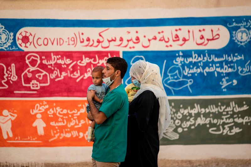 Syrians walk past a mural bearing instructions on protection from COVID-19 in Qamishli in  northeastern Syria on Aug. 16, 2020.
