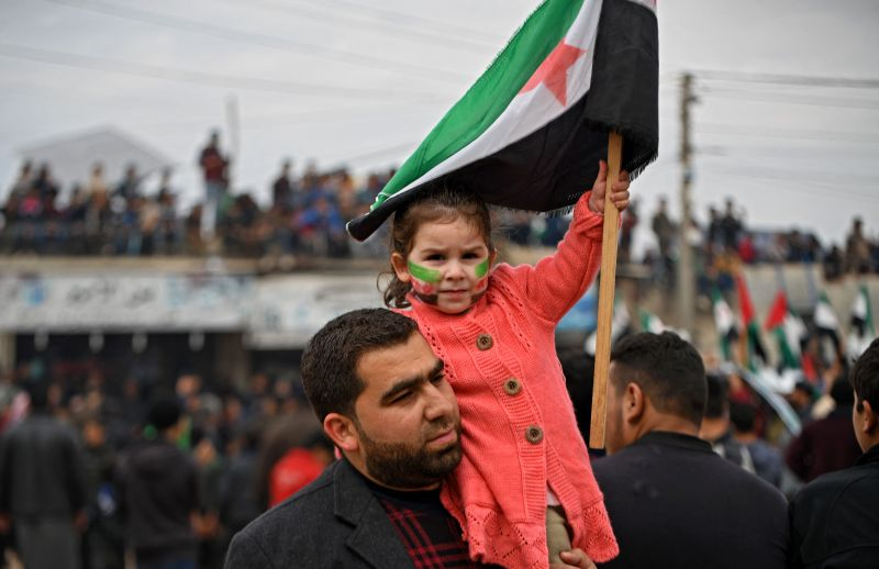 A man carries a girl on his shoulder as she holds a flag of the Syrian opposition during a protest in the village of Atme in Syria's northwestern province of Idlib on March 15.