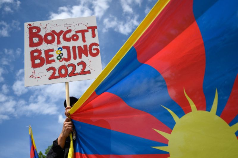 A Tibetan activist holds a placard and a Tibetan flag during a protest against Beijing 2022 Winter Olympics in front of the Olympics Museum in Lausanne on June 23.