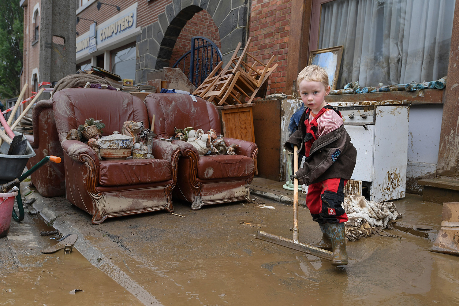 Boy cleans up mud from flooding in Belgium
