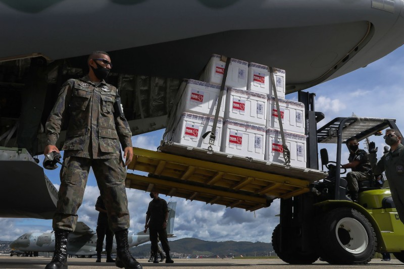 Military personnel offload COVID-19 doses.