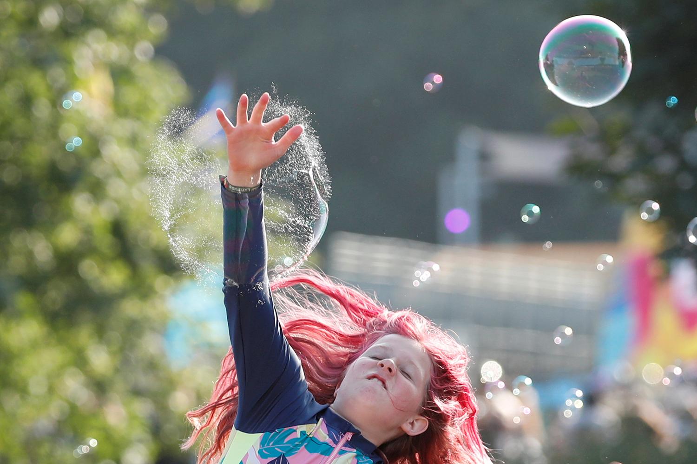 Girl pops a bubble at a festival in Britain