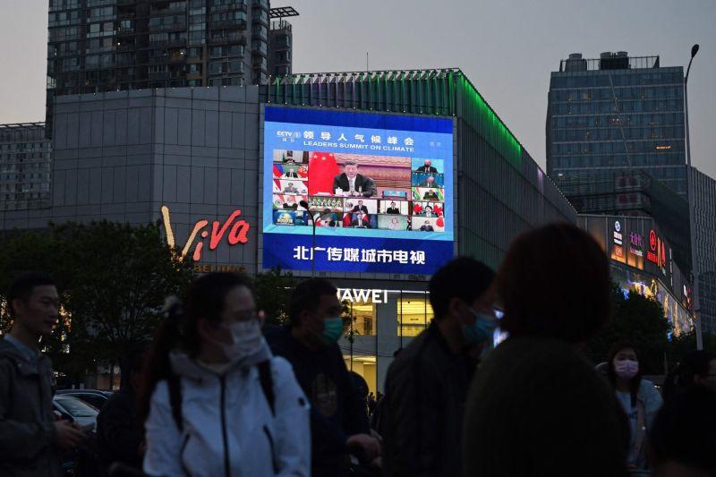 Chinese pedestrians watch the news.