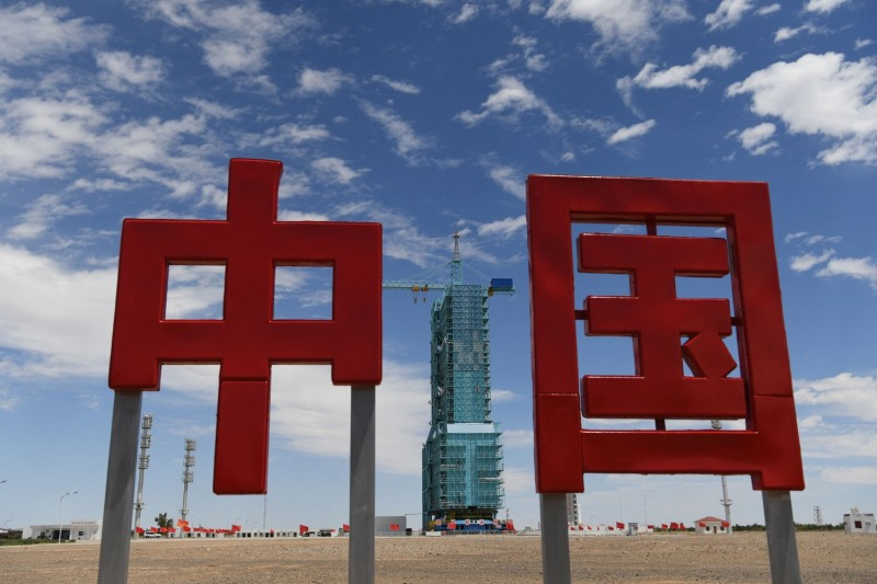 A Long March 2F rocket, carrying the Shenzhou-12 spacecraft for China's first crewed mission to its new space station, sits on a launch pad encased in a shield, behind the Chinese characters for China, at the Jiuquan Satellite Launch Center in the Gobi desert in northwestern China on June 16.