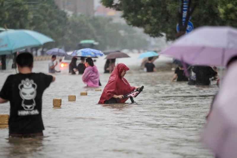 People wade through floodwaters along a street following heavy rains in Zhengzhou.