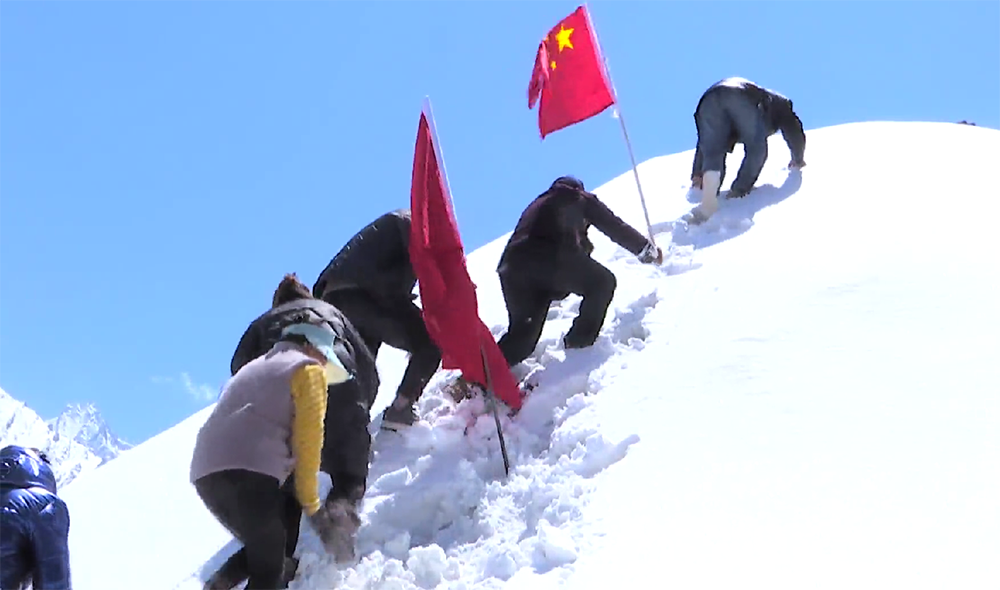Members of the Gyalaphug Joint Defense Team plant a flag on a peak in the Beyul, one of numerous similar images staged for official Chinese news photographers and filmmakers, on May 17.