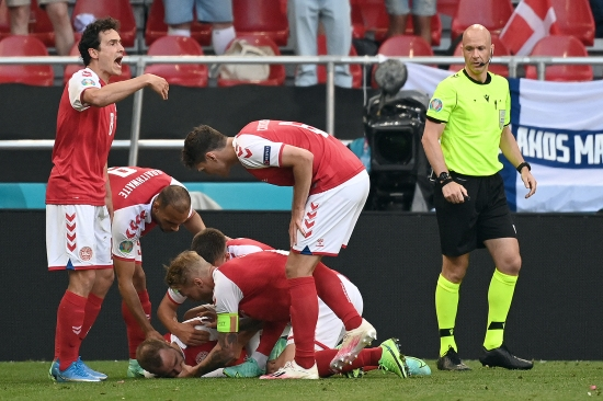 Denmark's players help midfielder Christian Eriksen after he collapsed on the pitch at a soccer game.