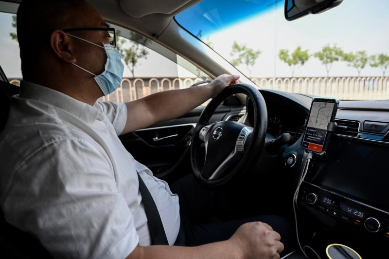 A driver uses the Didi app on his smartphone while driving along the street in Beijing.