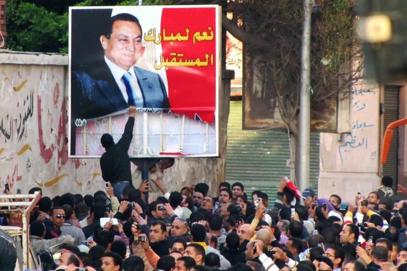 Egyptian demonstrators tear down a poster of Egyptian President Hosni Mubarak