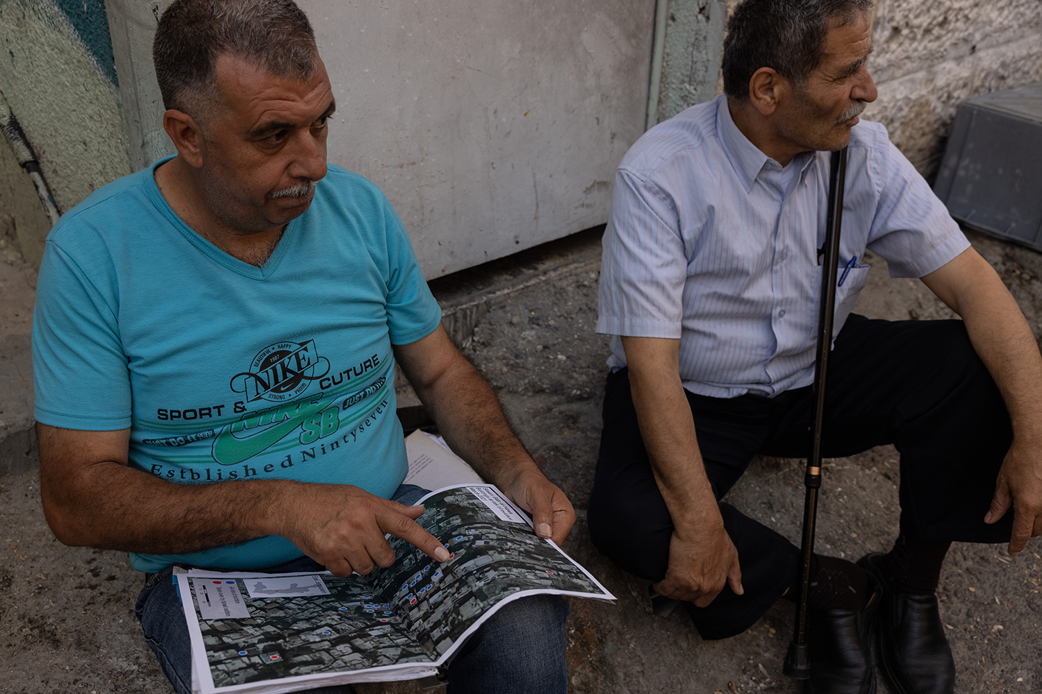 Zuhair Rajabi sits with a map outside his house in East Jerusalem on June 11. The map shows home evictions that have already gone through—and others that are threatened.