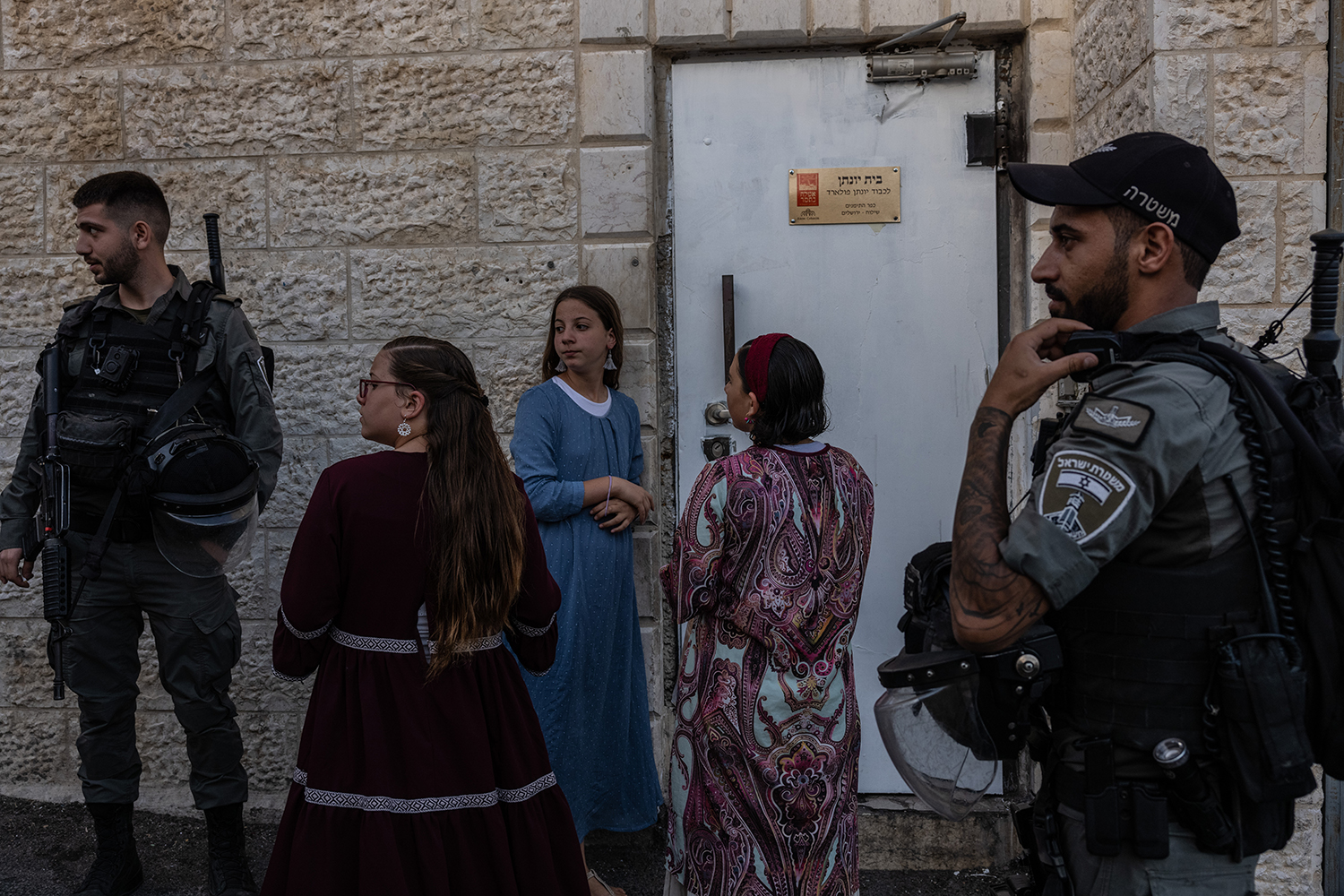 Jewish settlers who have moved to the Batan al-Hawa neighborhood are seen under police protection on June 14.
