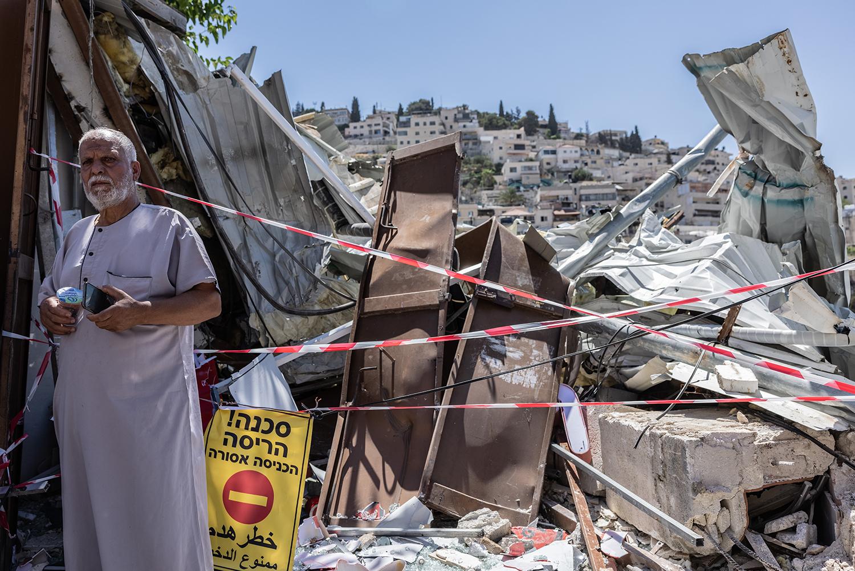 A man stands outside the ruins of Nidal Rajabi's house in East Jerusalem on June 29.
