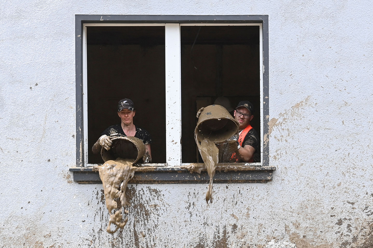 People dump out mud from house in Germany