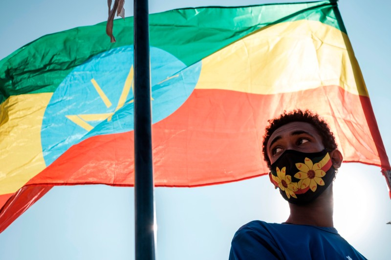 A young person stands below an Ethiopian national flag during a blood donation rally organized by the city administration of Addis Ababa, in Addis Ababa, on Nov. 12, 2020.