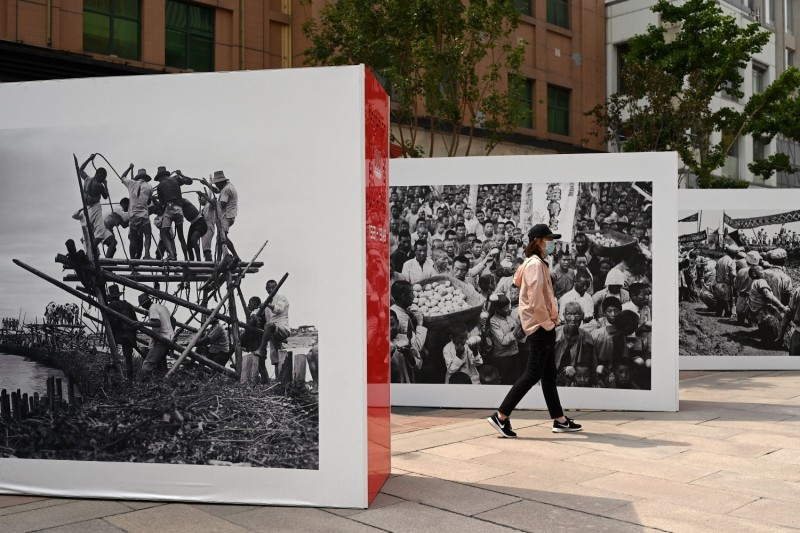 A man walks past an exhibit of Cultural Revolution pictures along Wangfujing shopping district in Beijing on June 12, 2021.