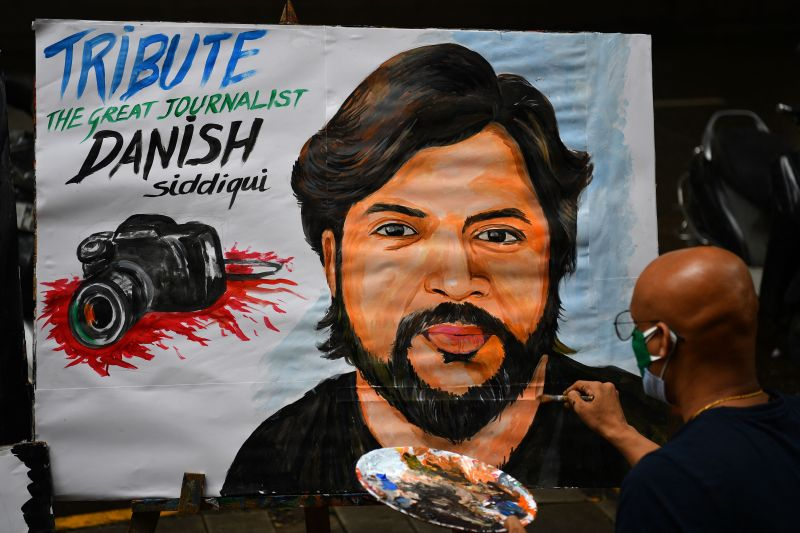An art teacher gives finishing touches to a painting of Reuters journalist Danish Siddiqui as a tribute outside an art school in Mumbai on July 16, 2021.
