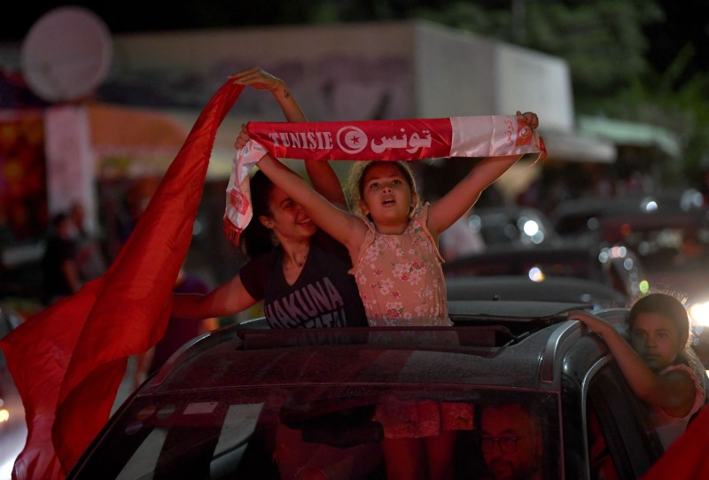 People celebrate in the streets of Tunis after Tunisian President Kais Saied announced the suspension of parliament and the dismissal of the prime minister on July 25, 2021, after a day of nationwide protests.