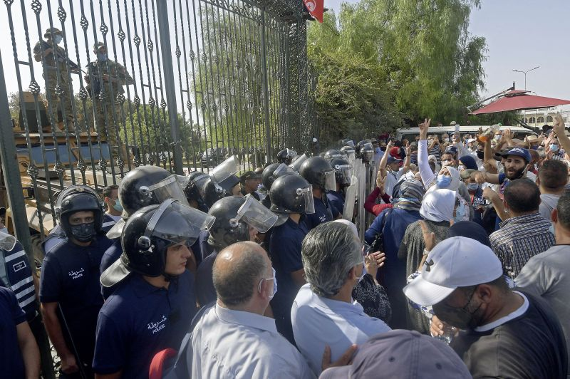 Tunisian security officers hold back supporters of the country's Islamist Ennahdha party during a protest outside the parliament building in the capital of Tunis.