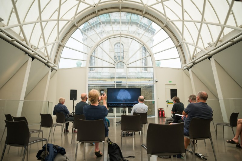 """Journalists and guests look on as a screen displays a part of the commissioned video installation """"I Saw The World End"""" by Artists Es Devlin and Machiko Weston at the Imperial War Museum in London on Aug. 6, 2020."""