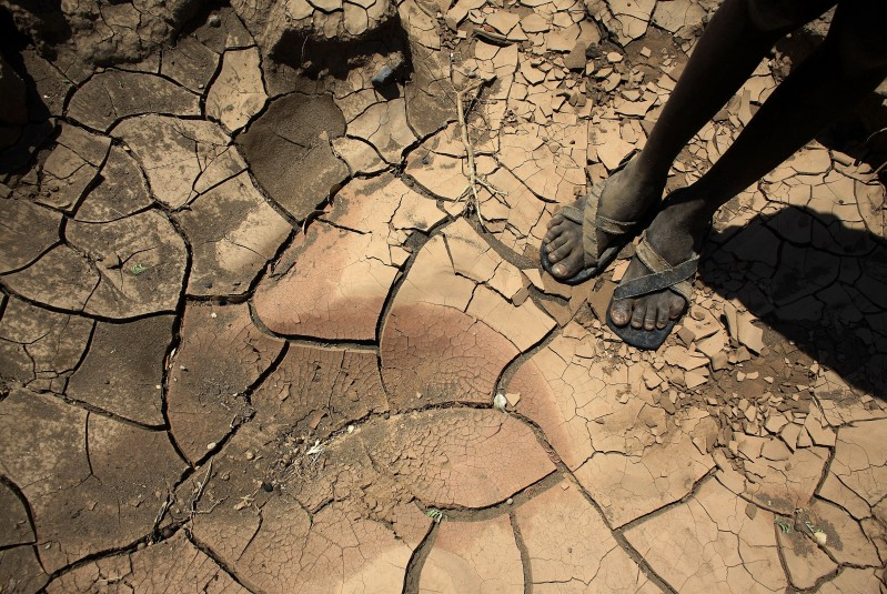 A boy stands by a dried riverbed in Kenya.