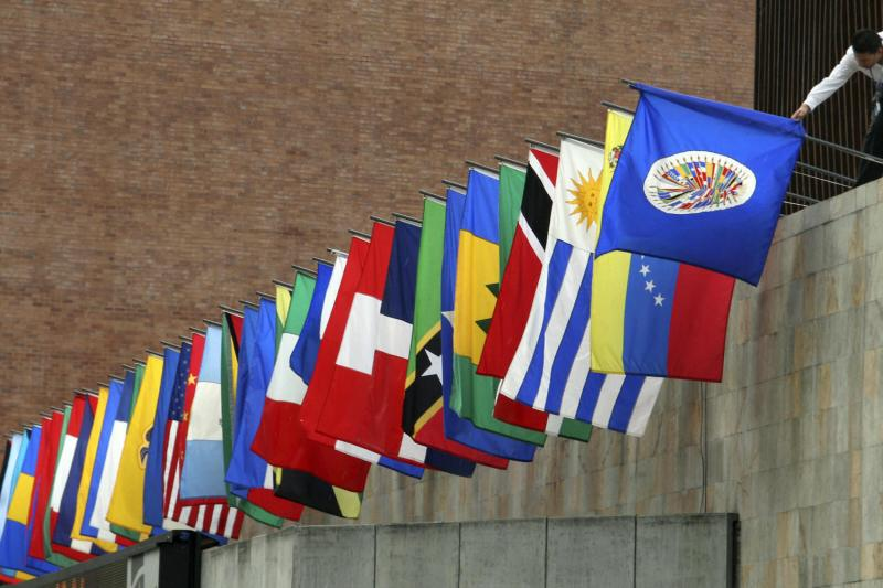 A worker prepares the flags of the Organization of American States (OAS) outside a press conference in Medellin on May 30, 2008.