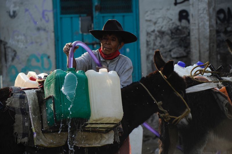 A woman fills containers with water from a public water pump, to take them home carried by her donkeys, in Santa Cruz Acalpixca, Xochimilco mayorality, Mexico City, on April 16.