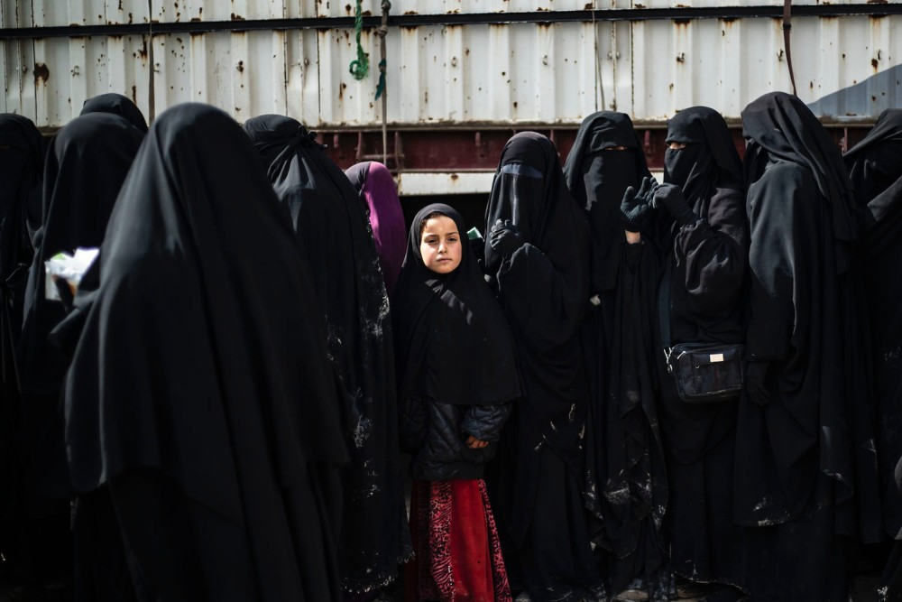 Refugees and displaced Syrian women living in al-Hol camp, which houses relatives of Islamic State group members, queue to receive goods in northeastern Syria on March 28, 2019.