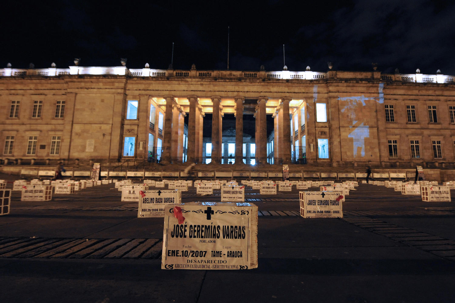 Picture of fake tombs placed in front of the Congress building during a protest against the false positives, massacres, and forced disappearances by Colombian authorities in Bogota on March 6, 2009.