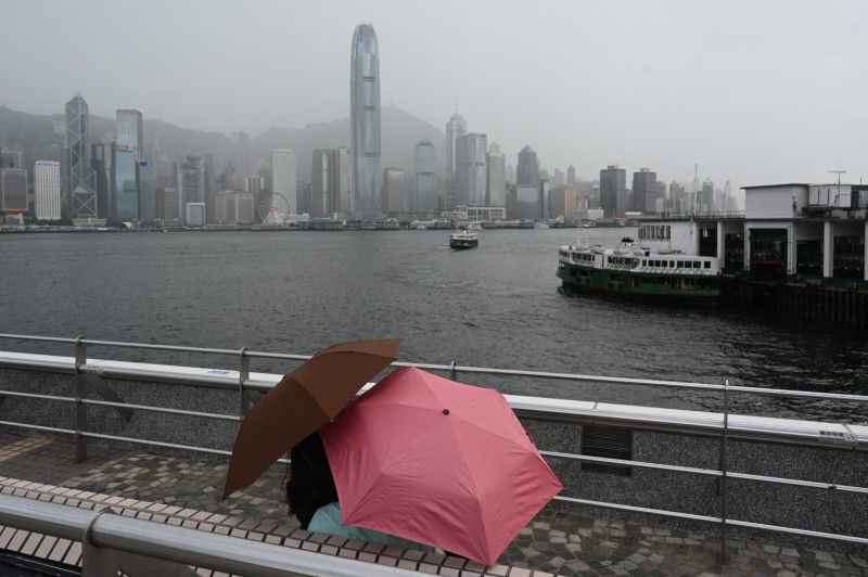 A couple shelters from the rain in Hong Kong.
