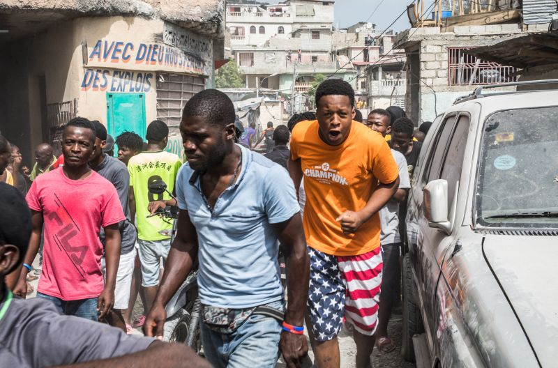 People help police arrest those accused of assassinating the Haitian president.