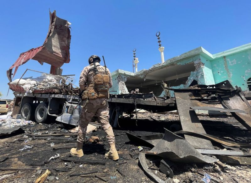 A member of the Iraqi security forces walks past a destroyed vehicle.