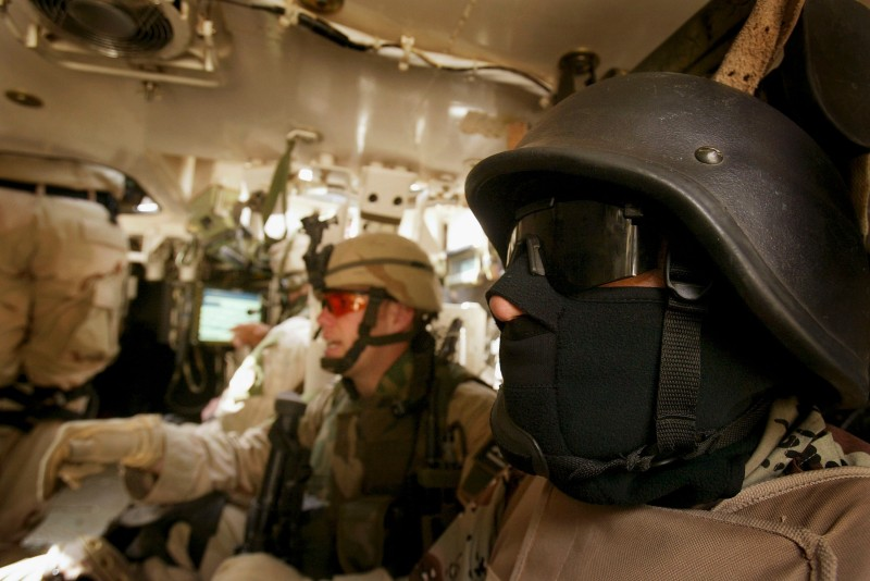 An Iraqi interpreter sits inside a vehicle with U.S. troops in 2005.