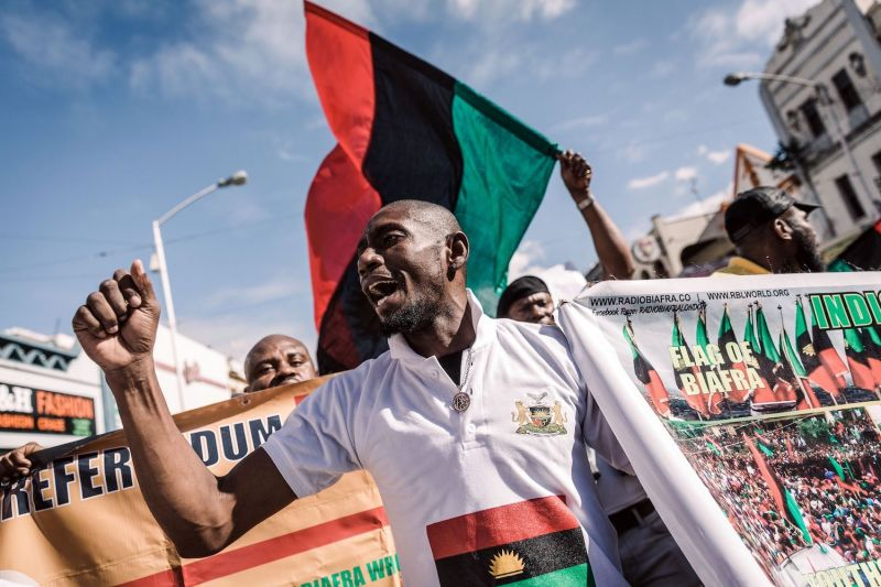 A protester holds a banner in front of a Biafra flag.