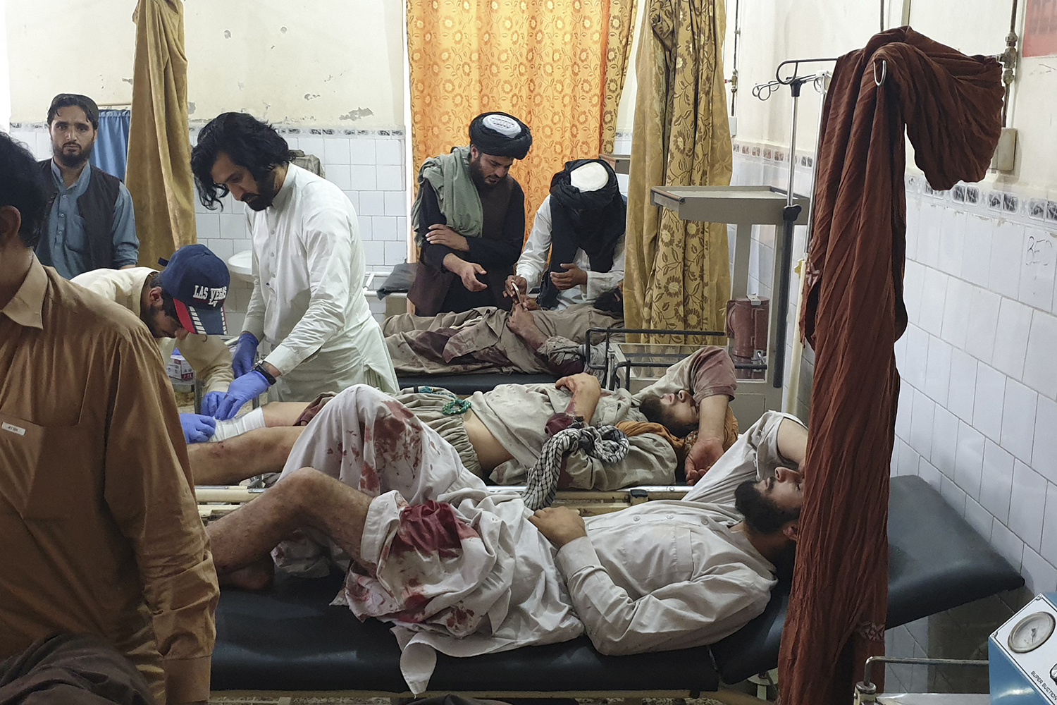 Paramedics treat men injured during fighting between Afghan forces and Taliban fighters