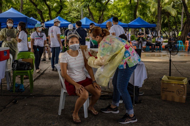 A public transportation worker is inoculated with Sinovac Biotech's CoronaVac COVID-19 vaccine during a mass vaccination event in Manila, the Philippines, on July 20.