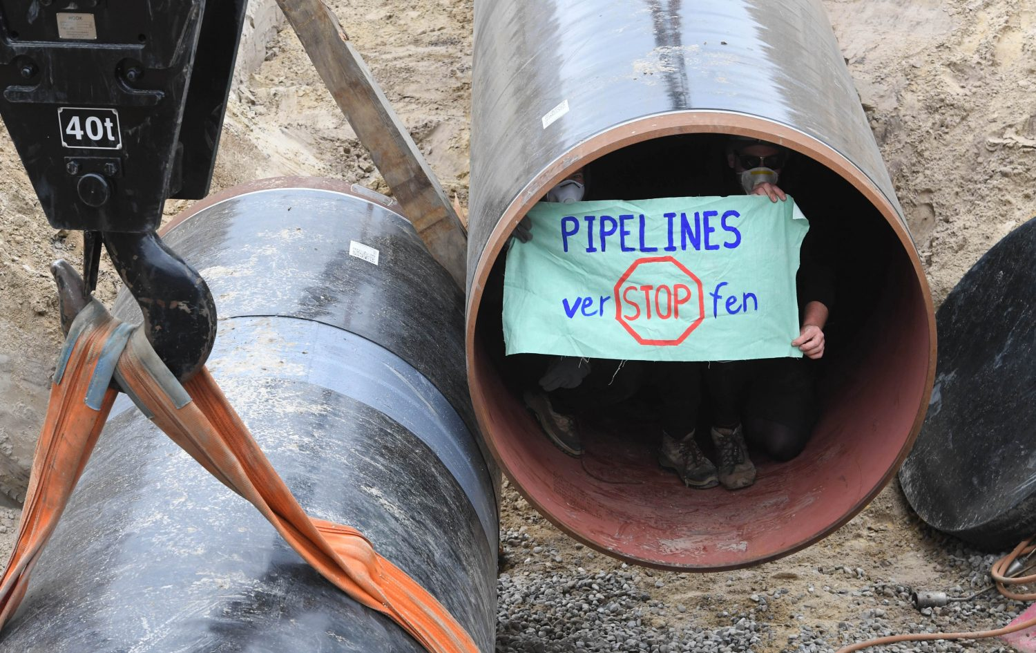 """Environmental activists hold up a poster reading """"Clog pipelines"""" as they sit in a tube on the construction site for the European Gas Pipeline Link, which will connect to Nord Stream 2, in Wrangelsburg, northeastern Germany, on May 16, 2019."""