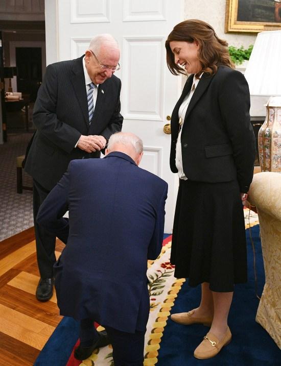 U.S. President Joe Biden kneels before Rivka Ravitz