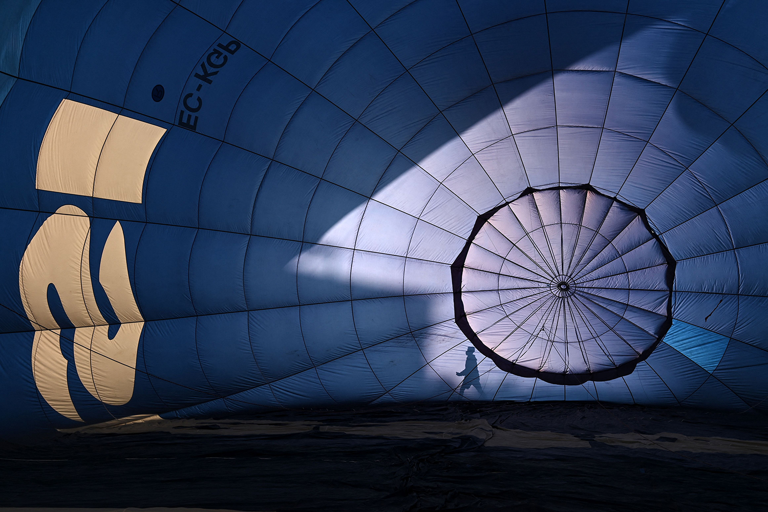 A person's shadow in front of hot air balloon at festival in Spain