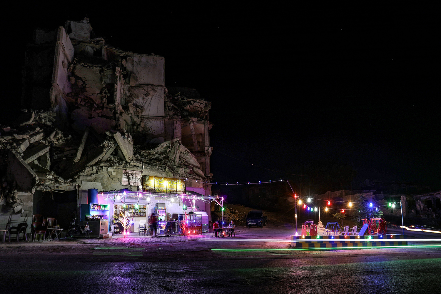 Cafe set up in front of destroyed building in Syria