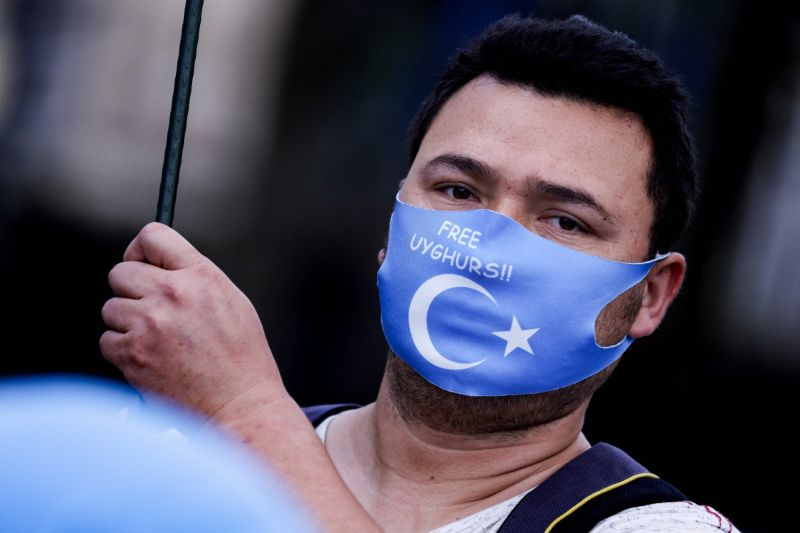 A demonstrator wears a mask with the East Turkestan flag